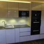 Küche, weiß hochglanz, grifflos mit indirekter LED-Beleuchtung, Arbeitsplatte: Vollkernplatte; schieferfarben