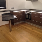 Küche mit indirekter Beleuchtung, Tisch und Arbeitsplatte aus Nero Assoluto