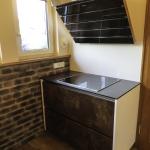 Küche, Kochecke, Front: Farbton Rusty, grifflos, Arbeitsplatte: Vollkernplatte; schieferfarben, GFK Steinpaneele Lodrillo Loft